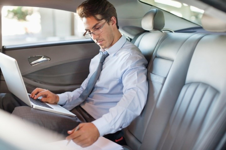 Business professional using laptop in car